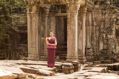 Cambodian Girl in Khmer Dress at Entrance to Ta Prohm, Angkor City. A Cambodian girl in a traditional Khmer dress stands by an ancient doorway at Ta Prohm Stock Images