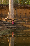 Cambodian Girl in Khmer Dress Sits by a Pool of Water in Angkor Thom Stock Images