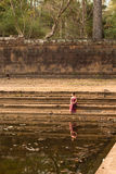 Asian Girl in Traditional Dress Sits by a Pool of Water in Angkor royalty free stock photo