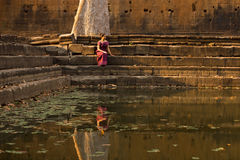Cambodian Girl in Khmer Dress Sits by a Pool of Water in Angkor Thom Royalty Free Stock Images