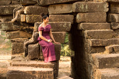 Cambodian Girl in Khmer Dress Sitting on a Bridge Over an Ancient Waterway in Angkor City Stock Photos