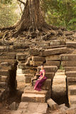 Cambodian Girl in Khmer Dress Sitting on a Bridge Over an Ancient Waterway in Angkor City Royalty Free Stock Image