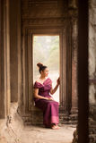 Cambodian Asian Girl in Traditional Dress Sitting in a Window in Angkor Wat Temple Stock Photography