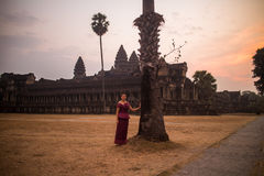 Cambodian Asian Girl in Traditional Dress by a Palm Tree at Angkor Wat Temple Royalty Free Stock Images