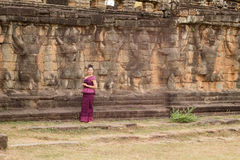 Cambodian Girl in Khmer Dress Standing at the Terrace of the Elephants in Angkor City Royalty Free Stock Images