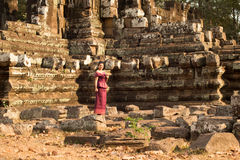 Cambodian Asian Girl in Traditional Dress by a Stone Temple Wall Stock Photography