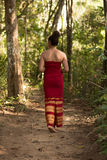 Asian Girl in Traditional Dress Walking a Path through the Jungle Royalty Free Stock Photos