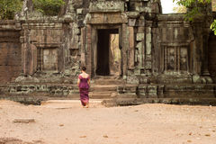 Cambodian Asian Girl in Traditional Dress Walks to the Doorway of a Temple Wall in Angkor Stock Photos