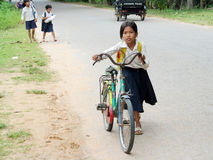 Cambodian little girl going to school by bicycle. Cambodian children, a little girl with books and bags going to school by bicycle, People living in Cambodia Royalty Free Stock Images