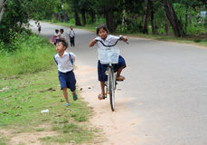 Cambodian little girl going to school by bicycle Royalty Free Stock Photography