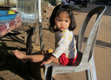 Cambodian little girl on the street. Small child sitting on the chair at the street market. People living in Cambodia. South east Asia Stock Photos
