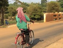 Cambodia Siem Reap Old Man on Bicycle. Cambodian local man riding his bicycle on a late afternoon on gravel road crossing a bridge stock photography