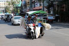 Cambodian male of sugarcane juice street vendor ride the three wheels motorcycle of his Kiosk that can move to various places royalty free stock photos
