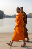 Cambodian monks smiling and walking to Angkor Wat Temple Royalty Free Stock Photo