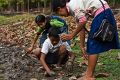 Cambodian mother, children dig worms Angkor Wat Royalty Free Stock Images