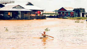 Cambodian people live on Tonle Sap Lake in Siem Reap, Cambodia. Cambodian boys use basin as a boat royalty free stock photo