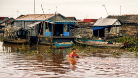 Cambodian people live on Tonle Sap Lake in Siem Reap, Cambodia. Cambodian boys use basin as a boat. Tonle Sap Lake Siem Reap, Cambodia - July 13, 2013: Cambodian Stock Images