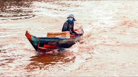 Cambodian people live on Tonle Sap Lake in Siem Reap, Cambodia. Woman riding on a motorboat Stock Photos