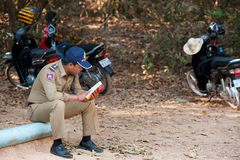 Cambodian policeman reads at Angkor Stock Images