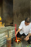Cambodian senior lighting incense in Angkor temple Stock Photos