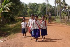Cambodian students walking on road. Cambodian little girls students in traditional clothes walking on a countryside dirt road near Siem Reap, Cambodia on Stock Photography