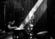 A Cambodian woman cooking in a market. Phnom Penh, Cambodia, December 25, 2007, A black and white photo of a Cambodian woman cooking in a market in Phnom Penh stock photo