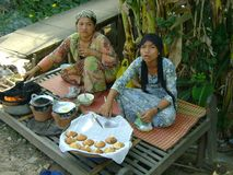 Cambodian women making and selling cakes. By the side of the road in traditional dress stock photos
