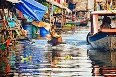 Cambodjaanse jongens die in een boot drijven stock fotografie