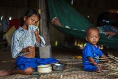 Cambodjaanse siblings die onder hun dorp zitten huisvesten Stock Fotografie