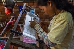 Cambodjaanse vrouwen wevende zijde bij een zijdelandbouwbedrijf Stock Afbeelding
