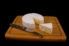 Cambozola cheese on black background. A slice of Cambozola cheese on a wooden board with a knife for soft cheese Stock Photos