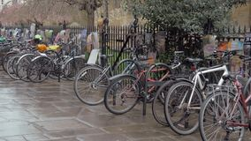 Bicycles parked against the railings with a lot of posters on it. Cambridge, England, 03 March 2019. Bicycles parked against the railings with a lot of posters stock video