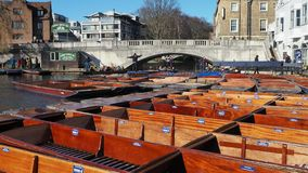 Cambridge, England. Tourists riding boat tours around the Cambridge University colleges along the river Cam. Group of empty wooden boats during the winter time stock video footage