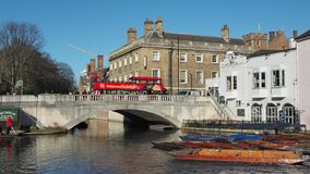 Cambridge, England. Tourists riding boat tours around the Cambridge University colleges along the river Cam. Group of empty wooden boats during the winter time stock video