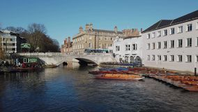 Cambridge, England. Tourists riding boat tours around the Cambridge University colleges along the river Cam. Group of empty wooden boats during the winter time stock footage