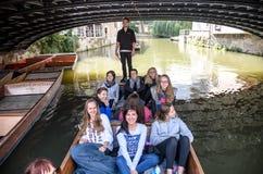 CAMBRIDGE UK - AUGUSTI 18: Yrkesmässig båtstakare i silvergata med den upptagna flodkammen mycket av turister i gondoler i bakgru Arkivbilder