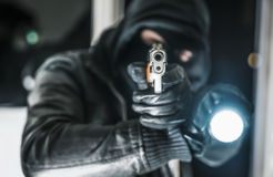 Cambrioleur avec l'arme à feu et la torche photographie stock