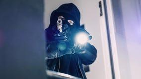 Cambrioleur avec l'arme à feu et la torche photo stock