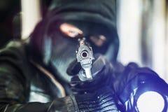 Cambrioleur avec l'arme à feu et la torche images libres de droits
