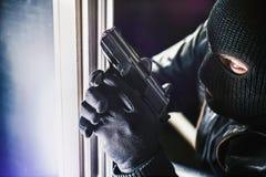 Cambrioleur avec l'arme à feu et la torche photos libres de droits