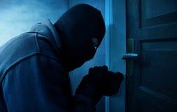 Cambrioleur masqué à l'aide de la récolteuse de serrure à la porte verrouillée ouverte images stock