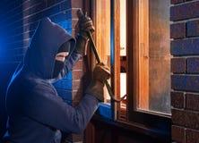 Cambrioleur pénétrant par effraction dans une maison Image libre de droits
