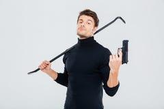 Cambrioleur sûr de jeune homme posant avec l'arme à feu et le pied-de-biche image stock