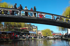 Camden Lock, London. A busy and vibrant Camden Lock in north London on a bright spring day. People eating and rinking on bridge and canal bank with red london Stock Images