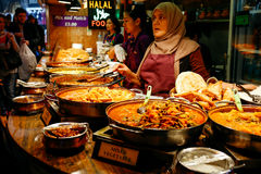 Camden Market. Traders at a market stall selling curry and variety of cooked foods at Camden Market, London Royalty Free Stock Photos