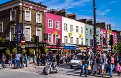 Camden Town. London, UK. There are a lot of colorful buildings, vehicles on the street and a crowd of visitors in a sunny day Stock Images