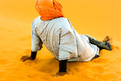 Camel driver resting on sand dune after work Royalty Free Stock Photo