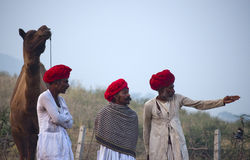 The camel herders with red turbans. Camel traders of Pushkar, Rajasthan, India wearing red turbans and standing with the camel in the fair ground Royalty Free Stock Image
