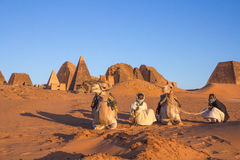 Camel and his cameleer. Khartoum, Sudan - Dec 19, 2015: Cameleer posing with his camel at sunrise ahead of the pyramids stock photo