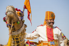 Camel and indian men wearing traditional Rajasthani dress participate in Mr. Desert contest as part of Desert Festival in Jaisalme. JAISALMER, INDIA - FEBRUARY Stock Photos